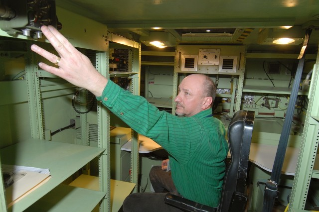 John Sedeski makes final adjustments to the vehicular intercom system, which enables communication from the Standard Integrated Command Post Shelter to the cab of the Humvee.  Sedeski is an electronics technician at Tobyhanna Army Depot.