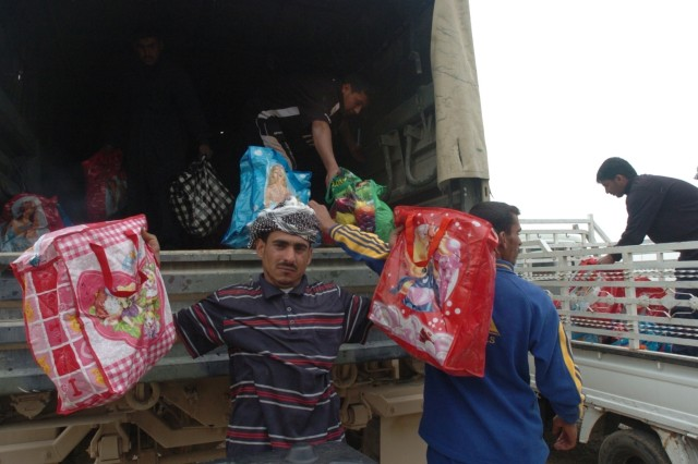 Members of the Mamouri and Khazraj tribes receive food assistance bags March 11 just outside Patrol Base Copper, Iraq. One bag can sustain a family of four for a week's period and contains rice, beans, sugar, cooking oil, tea, tomato paste and spices.