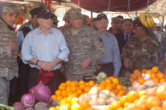 Senator John McCain, of Arizona; Maj. Gen. Rick Lynch, commander of the 3rd Infantry Division; and Senator Joseph Lieberman, of Connecticut, check out a fruit stand in the marketplace in Iskandariyah, Iraq, March 17.