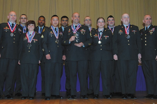 The Fort Carson team, winner of the Installation of the Year Award, poses with Brig. Gen. Jesse R. Cross (FAR LEFT), Quartermaster Center and School commanding general, and Command Sgt. Maj. Nathan Hunt (FAR RIGHT), the school's top enlisted Soldier at the awards ceremony concluding the 33rd U.S. Army Culinary Arts Competition at Fort Lee, Va.
