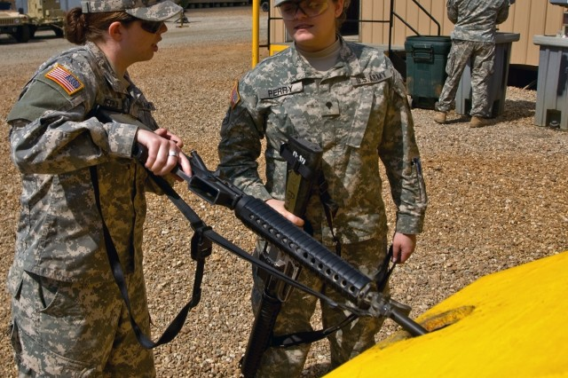 Spc. Cassandra Perry inspects fellow intelligence analyst Pfc. Karen Medlin's weapon at a clearing barrel before entering the Forward Operating Base Sword dining facility for lunch March 14. The clearing barrels at the Joint Readiness Training Center are for 4th Brigade Combat Team Soldiers to develop the habit of clearing their weapons prior to entering buildings.