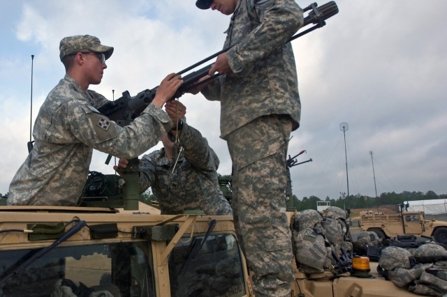 Sgt. Blake Brandenburg, Sgt. Steve Robinson and Spc. David Williams, forward observers assigned to the 4th Brigade Combat Team's personal security detachment install a .50 caliber machine gun to a vehicle. The 1st Cavalry Division's new Long Knife Brigade is training at the Joint Readiness Training Center in Fort Polk, La.