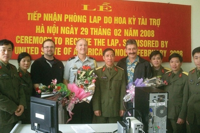 Caption 2:  From left, John Nemeth, Col. Mark B. Chakwin, and Richard Ondreko stand with representatives of the Vietnamese army's Regimen 871 after a handover ceremony of a language lab.  Chakwin is Defense and Army Attache security cooperation officer, American Embassy, Hanoi.  Nemeth is an electronics technician in the Command, Control and Computers/Avionics Directorate.