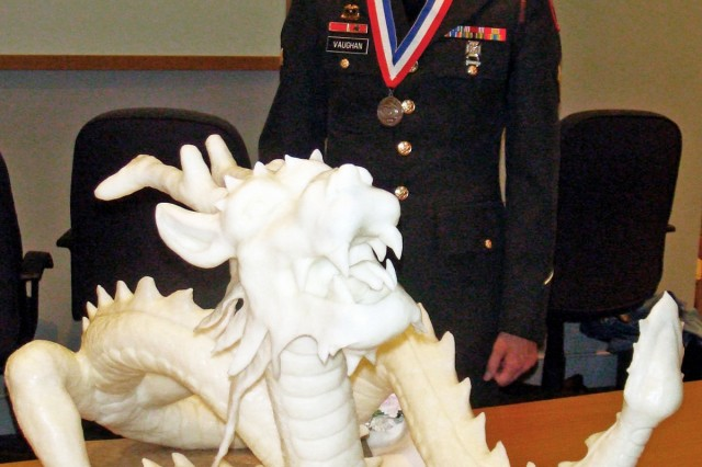 Spc. Jeffrey Vaughn of the 3rd U.S. Infantry stands behind his white-chocolate dragon at the Army Culinary Arts Competition after winning a silver medal in the Centerpiece category.