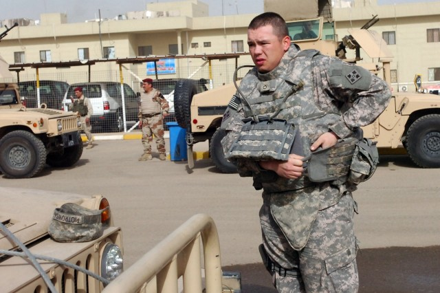 Pfc. Joe Piotrowski, with the 6th Iraqi Army Division Military Transition Team, 4th Infantry Division, dons his Improved Outer Tactical Vest on March 14 before a mission in Baghdad.  He said the new vest is more comfortable than the Interceptor Body Armor and has a better carrying system for his equipment.