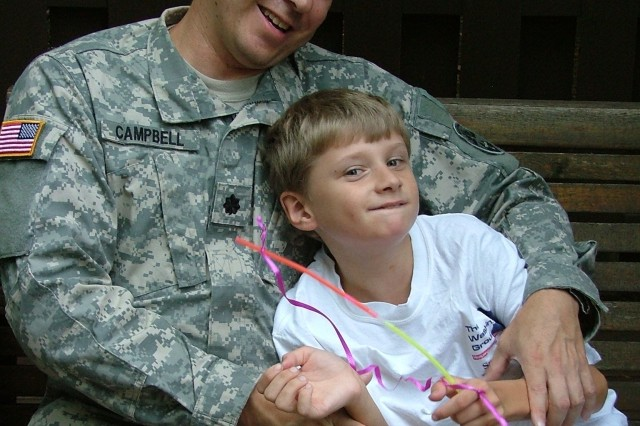 Lt. Col. Scott Campbell sits with his son, Ian. After struggling to get proper care for Ian, who is autistic, Campbell spearheaded a campaign for better treatment options for military families.