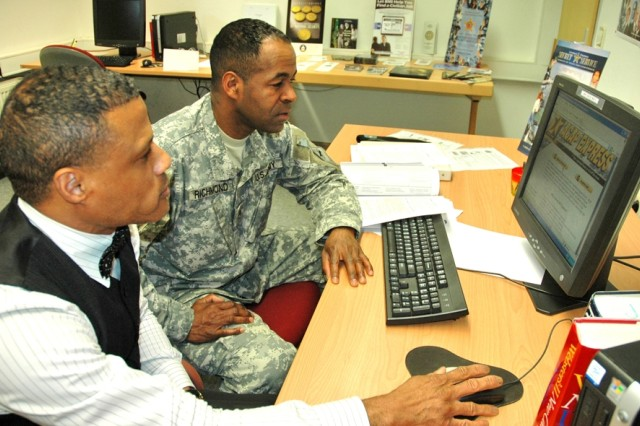 Daniel Strong, left, of the Wiesbaden Army Career and Alumni Program, describes the features of the new online ACAP Express to Staff Sgt. Lester Richmond.