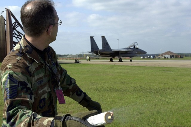 U.S. Air Force Senior Master Sgt. Gregory Fazah, Wing Readiness Evaluator assigned to the 48th Fighter Wing, prepares to throw an M115A2 to initiate a simulated attack on a USAF F-15 Eagle aircraft, during the 48th Fighter Wing Tactical Evaluation Exercise held at Royal Air Force Feltwell, United Kingdom.
