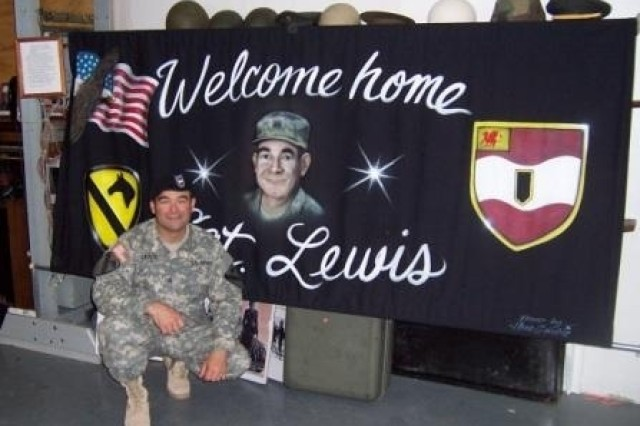 Sgt. Troy Lewis, a self-propelled artillery mechanic with Company G, 3rd Battalion, 82nd Field Artillery, 2nd Brigade Combat Team, 1st Cavalry Division. poses in front of a welcome home sign that his family made for him Jan. 31.
