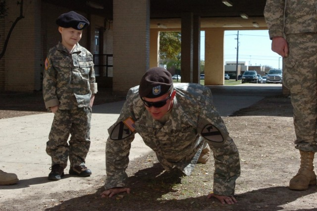 Recently-promoted Staff Sgt. Gaven Cox gives Sgt. David Raines the order to do push-ups after he is promoted during a formation at Fort Hood, Texas, March 20. Raines, a cavalry scout with Troop C, 6th Squadron, 9th Cavalry Regiment, 3rd Brigade Combat Team, 1st Cavalry Division, said he just wanted Gaven to walk away with a smile on his face.