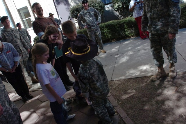 Recently-promoted Staff Sgt. Gaven Cox's family members, mother Melissa Heminger, stepfather Troy Heminger, 10-year-old brother Chandler Zeemer, 8-year-old sister Jade Cox, and 4-year-old brother Zayne Cox, greet him after his promotion ceremony at Fort Hood, Texas, March 20.