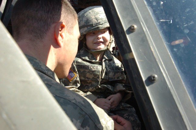 Staff Sgt. Gaven Cox, a 5-year-old who was diagnosed with leukemia, checks out the pilot seat with the help of Spc. Andrew Ramsdell a crew chief with Company C, 3rd Assault Helicopter Battalion, 227th Aviation Regiment, 1st Air Cavalry Brigade, 1st Cavalry Division, on Fort Hood, Texas, March 20.