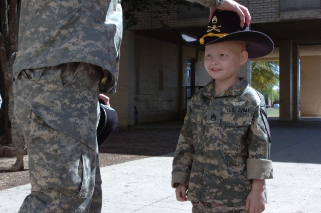 A cancer patient Staff Sgt. Gaven Cox is presented a Stetson, a tradition unique to the 1st Cavalry Division, after being promoted during a formation at Fort Hood, Texas, March 20. Cox will be turning six in early April and it was his wish to become a story.