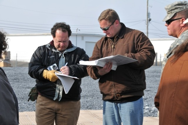 Jerry O'Keefe, left, and Doug Cheney, of Product Manager, Tactical Operations Centers, validate the setup of a tent and make notes of exceptions in the process during the initial stages of Operation TOCFEST March 7 at Fort Indiantown Gap, Pa.