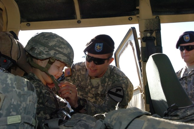 Sgt. David Raines straps on Gaven Cox's helmet before the 5-year-old's day starts at Fort Hood, Texas, March 20.