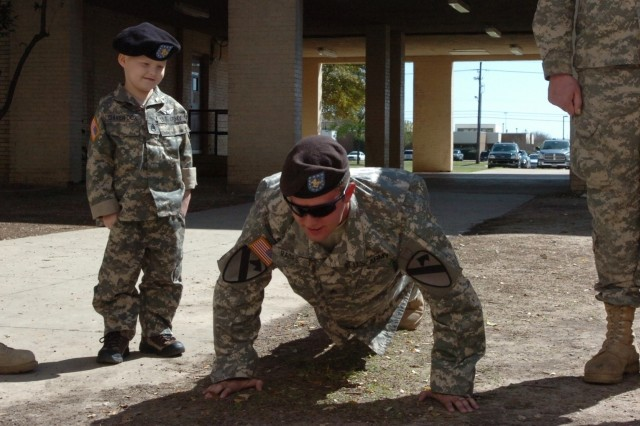 Recently-promoted 5-year-old Staff Sgt. Gaven Cox gives Sgt. David Raines the order to do push-ups after the promotion during a formation at Fort Hood, Texas, March 20.