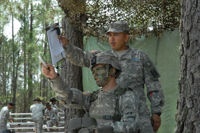 Sgt. 1st Class Juan Barrera, Company C, 3rd Infantry Battalion, 60th Infantry Regiment instructor, points out targets to Staff Sgt. James Hawkins, Company C, 3rd Battalion, 34th Infantry Regiment at the range estimation station during the Expert Infantry Badge testing Tuesday. Candidates have to estimate the range using binoculars.