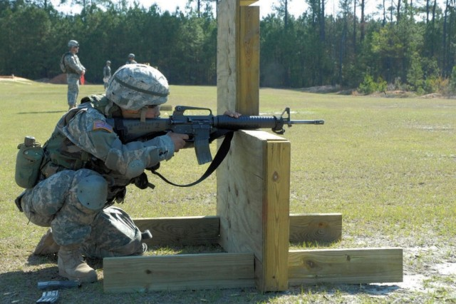 "Pvt. Abby Anthony, Company C, 2nd Battalion, 39th Infantry Regiment, kneels behind an L-shaped barrier on Range 10 during ""Combat Shoot,"" an experimental Basic Rifle Marksmanship qualification course."