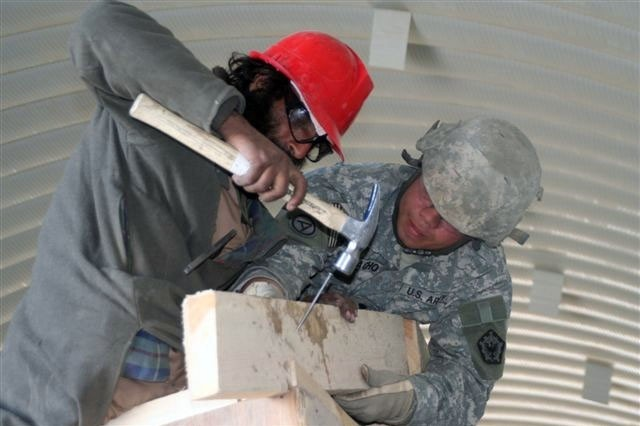 Army Spc. Angel Camacho, 585th Engineer Company, Fort Lewis, Wash., guides an Afghan as he nails a rafter in place during a skilled-labor workshop at Forward Operating Base Sharana, Paktika Province, Afghanistan.