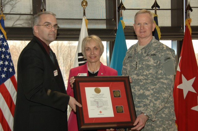 Margaret Moug (center) is presented the Yongsan Red Cross Volunteer of the Year award by Douglas Timpson, Yongsan Red Cross senior station manager, and Gen. B.B. Bell, commander, U.S. Forces Korea and Combined Forces Command.