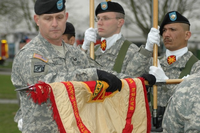 Col. Robert Ulses unfurls the guidon of his newly renamed command, U.S. Army Garrison Baden WAfA1/4rttemberg, during a renaming ceremony in Heidelberg, Germany, March 27.