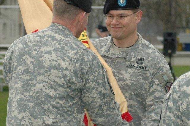 New U.S. Army Garrison Heidelberg commander, Lt. Col. Robert White, accepts the colors of the indirect reporting garrison in a March 27 ceremony from Col. Robert Ulses, who moments before had unfurled the colors of his new direct reporting garrison, USAG Baden-Wurttemberg.