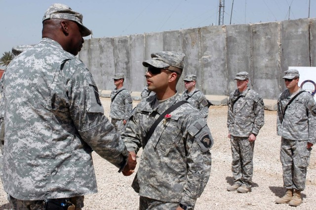 Lt. Gen. Lloyd J. Austin III, commanding general, Multi-National Corps-Iraq presents Pvt. Erick Rodriguez, medic, Company B, 2nd Battalion, 502nd Infantry Regiment, 4th Brigade Combat Team, 3rd Infantry Division, with a bronze star for valor at Forward Operating Base Kalsu March 20.