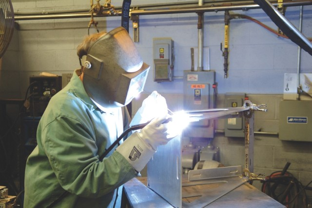 Robin Meckes welds a component for a mine resistant ambush protected vehicle kits. Meckes is a welder in the Systems Integration and Support Directorate.