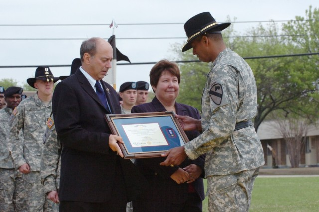 Brig. Gen. (P) Vincent Brooks, the commanding general of the 1st Cavalry Division, presents the Silver Star, the nation's third-highest award for valor, to the parents of Capt. Mark Resh, Charlie and Carol Resh from Fogelsville, Va., during a ceremony held at Fort Hood, Texas's Cooper Field March 26.