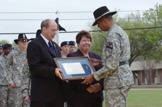 Brig. Gen. (P) Vincent Brooks, the commanding general of the 1st Cavalry Division, presents the Silver Star, the nation's third-highest award for valor, to the parents of Capt. Mark Resh, Charlie and Carol Resh from Fogelsville, Va., during a ceremon...