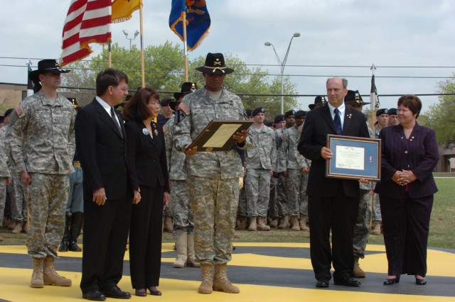 Brig. Gen. (P) Vincent Brooks, the commanding general of the 1st Cavalry Division, presents the Silver Star, the nation's third-highest award for valor, to the parents of Capt. Mark Resh and Chief Warrant Officer 3 Cornell Chao, both Apache pilots with the division's 4th Battalion, 227th Aviation Regiment, 1st Air Cavalry Brigade, during a ceremony held at Fort Hood's Cooper Field March 26. Chao's stepfather Glen Crowl and mother Jasmine Crowl from Orange City, Calif., are pictured on the left and Resh's father Charlie Resh and mother Carol Resh, from Fogelsville, Va., are pictured on the right.