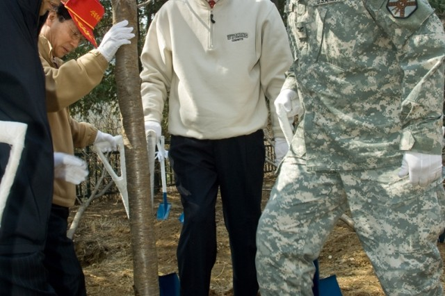 Col. Dave Hall, USAG-Yongsan commander, and Park Jang-kyu, Yongsan District mayor, finish planting a cherry tree at the Namsan Botanical Garden in Seoul.