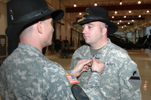 """Las Vegas native Lt. Col. Christopher Walach (right), commander of the 1st """"Attack"""" Battalion, 227th Aviation Regiment, 1st Air Cavalry Brigade, 1st Cavalry Division, pins an Air Medal with """"V"""" device for Valor onto Fort Pierce, Fla., native Capt. Paul Daigle, an AH-64D Apache attack helicopter pilot for Company C, 1-227th. Daigle received this award for his actions July 23 when he helped aid a joint combat outpost that was on the verge of being overrun by insurgents."""