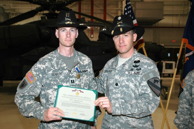 """Las Vegas native Lt. Col. Christopher Walach (right), commander of the 1st """"Attack"""" Battalion, 227th Aviation Regiment, 1st Air Cavalry Brigade, 1st Cavalry Division, presents Capt. Nathan Schmidt (left), commander of Company C, 1-227th, with an Air Medal with """"V"""" device for Valor during an awards ceremony March 18 at Fort Hood, Texas. Schmidt, who hails from Norfolk, Va., helped fend off insurgents from overrunning a joint combat outpost July 23."""