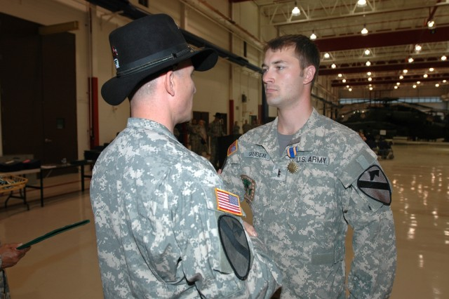 """Las Vegas, native Lt. Col. Christopher Walach, commander of the 1st """"Attack"""" Battalion, 227th Aviation Regiment, 1st Air Cavalry Brigade, 1st Cavalry Division, shakes the hand of Freeport, Pa., native Chief Warrant Officer 2 Brent Gruber, an AH-64D Apache attack helicopter pilot for Company C, 1-227th, after awarding him the Air Medal with Valor during an awards ceremony March 18 at Fort Hood, Texas. Gruber earned his award July 6 when he gave up his seat in his Apache to help evacuate an injured special operations team member to a combat support hospital after an improvised explosive device attack."""