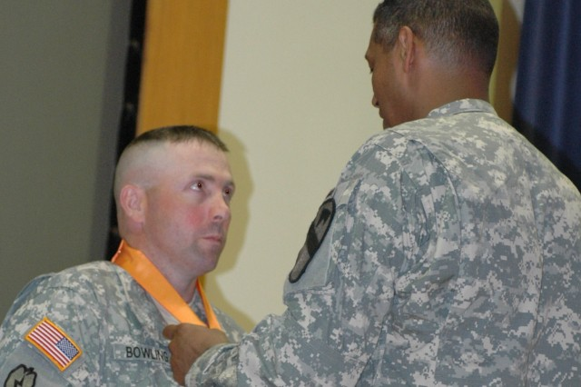 Staff Sgt. Shannon Bowling, an enhanced position location reporting system manager, receives the medal for the Bronze Order of Mercury from his commanding general Brig. Gen. (P) Vincent K. Brooks, at a ceremony in the Fort Hood Battle Simulation Center March 25. Bowling and four other 1st Cavalry Division Soldiers were presented the medal for contributing to the Signal Corps Regiment.