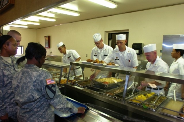 Troops from the 2nd Brigade Combat Team, 1st Cavalry Division, get hot food served up during the grand opening of the Black Jack Inn dining facility On Fort Hood, Texas, April 1.