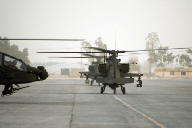 AH-64D Apache Longbow attack helicopters from Task Force XII prepare to take off from Camp Taji, Iraq on a mission in the Baghdad region.