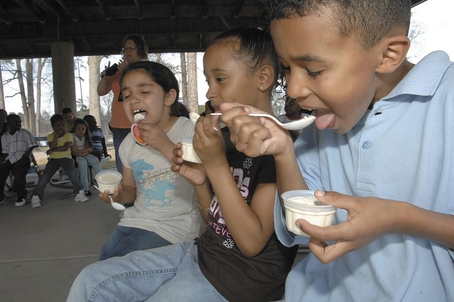 Breauna Johnson, Alexia Williams and Tynan Bassett dig in and scoop up during the ice cream social April 1 during Fort Lee's celebration of the Month of the Military Child.