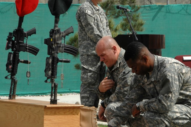 BAGRAM AIRBASE, Afghanistan- 3rd Special Forces Group (Airborne) Commander Col Christopher K. Haas and CJSOTF-A Support Command Sgt. Major, Command Sgt Maj. Edward A. Bell, pay their respects to their fallen comrades Staff Sgt. William Neil, Special Forces engineer and Tech. Sgt. William Jefferson Jr and Air Force Combat Controller, during a memorial ceremony at Bagram Airbase, March 27.  Both men died in combat March 22, 2008 while conducting combat operation near Sperwan Ghar, Afghanistan.  (CJSOTF-A photo by SSG Marie Schult)