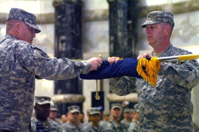 Command Sgt. Maj. Brian Sann, outgoing command sergeant major, 58th Infantry Brigade Combat Team, and Col. Sean Casey, outgoing commander, 58th IBCT, case their colors as part of their transfer of authority ceremony March 26 at Al Faw Palace.