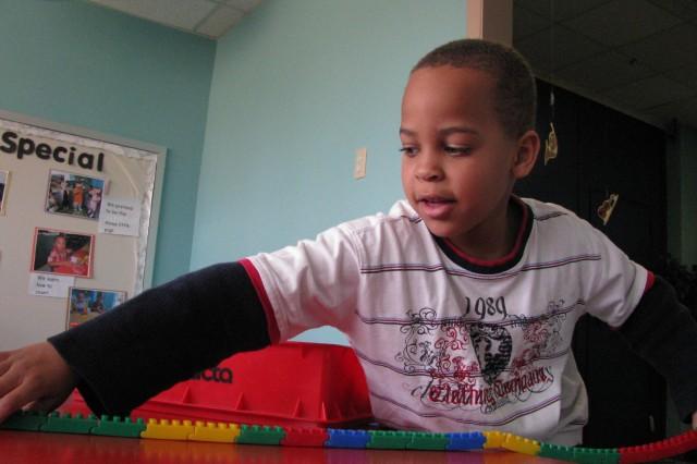 Jael Kelley 5, a preschooler at the Child Development Center, reaches for flexi-blocks. HeAca,!a,,cs the son of Air Force recruiter Staff Sgt. Jerry Kelley and Arlene Kelley.