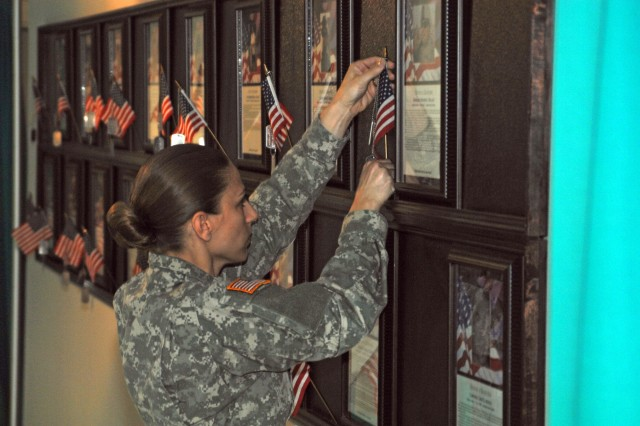 Staff Sgt. Aimie Robins of HRC-St. Louis places a flag on the command's memorial wall next to the photo and biography of an Individual Ready Reserve Soldier killed in action.