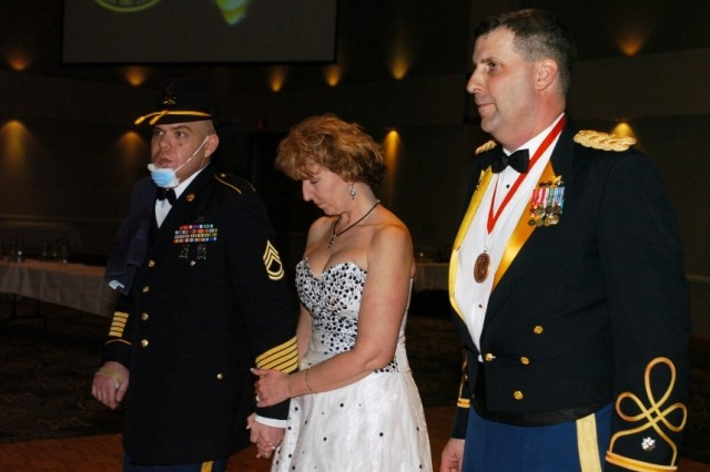 Sgt. 1st Class Carl Pasco (left) and his wife Joy were recently honored by Lt. Col. Jeffrey Sauer, commander 1st Battalion, 8th Cavalry Regiment, during the Mustang's ball event March 12. Carl was awarded a purple heart and a bronze star and Joy was recognized for her work with the battalion's family readiness group.