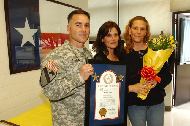Michelle Linard (right), poses with Lt. Col. Michael Tarsa, the commander of the 3rd Battalion, 82nd Field Artillery, 2nd Brigade Combat Team, 1st Cavalry Division and his wife Linda after being presented with The State of Texas Governor's Yellow Rose of Texas Commission. The Yellow Rose of Texas is awarded to Texas women in recognition of their lengthy community involvement, and was presented to Linard during a volunteer recognition ceremony hosted by 3-82 FA at Fort Hood's Soldier and Family Readiness Center April 3.