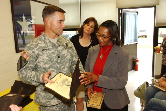 Charmaine Milford (right) is presented an award for her work with 3rd Battalion, 82nd Field Artillery's Family Readiness Group by the battalion's commander, Lt. Col. Michael Tarsa, while Tarsa's wife Linda looks on April 2. Several family members were honored during a volunteer recognition ceremony at Fort Hood's Soldier and Family Readiness Center that was hosted by 3-82 FA, which is a part of the 2nd Brigade Combat Team, 1st Cavalry Division.