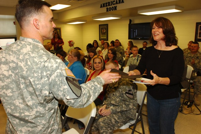 The commander of the 3rd Battalion, 82nd Field Artillery, 2nd Brigade Combat Team, 1st Cavalry Division, Lt. Col. Michael Tarsa, presents an award to Debbie O'Donnell for her contributions with the unit's Family Readiness Group. O'Donnell was one of several family members honored during a volunteer recognition ceremony at Fort Hood's Soldier and Family Readiness Center April 2.