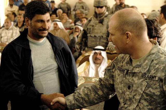 Lt. Col. Thomas  Boccardi, commander, 1st Battalion, 14th Infantry Regiment, 2nd Stryker Brigade Combat Team, 25th Infantry Division, shakes hands with a recently released detainee during a reconciliation ceremony at an Iraqi police station in Tarmiya, March 19, 2008.
