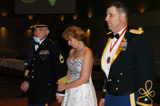 Sgt. 1st Class Carl Pasco (left) and his wife Joy were recently honored by Lt. Col. Jeffrey Sauer, commander 1st Battalion, 8th Cavalry Regiment, during the Mustang's ball on March 12. Carl was awarded a Purple Heart and a Bronze Star, and Joy was recognized for her work with the battalion's Family readiness group.