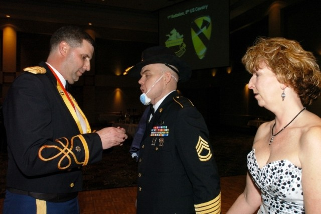 Sgt. 1st Class Carl Pasco is awarded a Purple Heart and a Bronze Star by his battalion commander, Lt. Col. Jeffrey Sauer, while his wife Joy watches, during the 1st Battalion, 8th Cavalry Regiment\'s ball March 12.